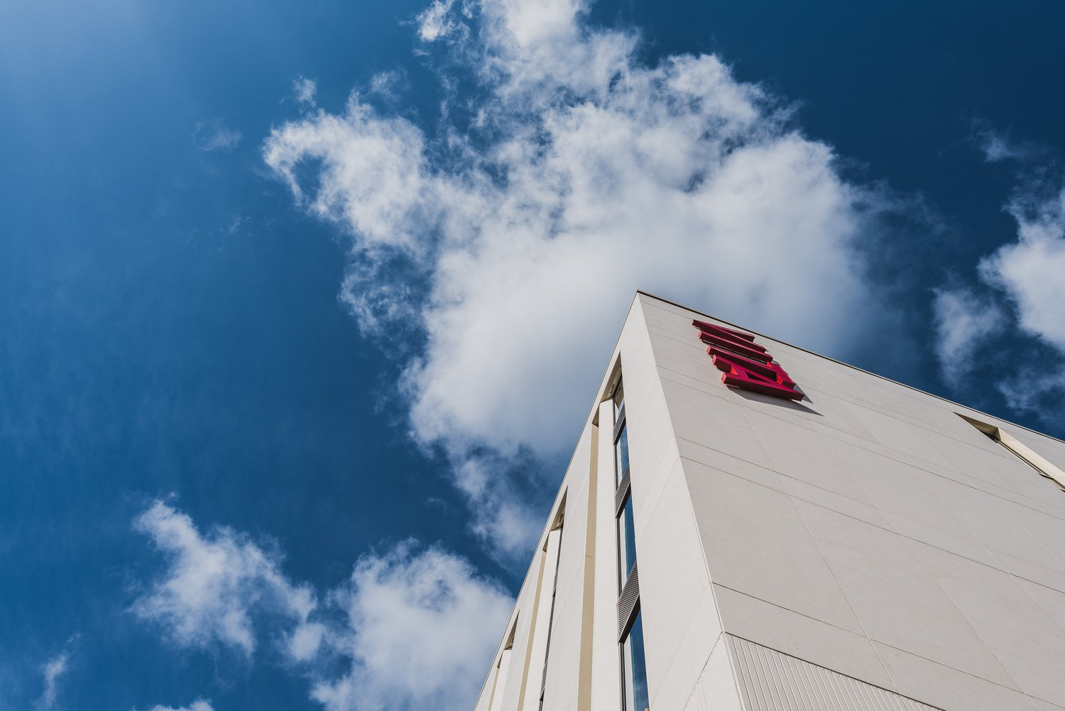 Low angle shot of VITA Birmingham, corner of the building against a blue sky with clouds