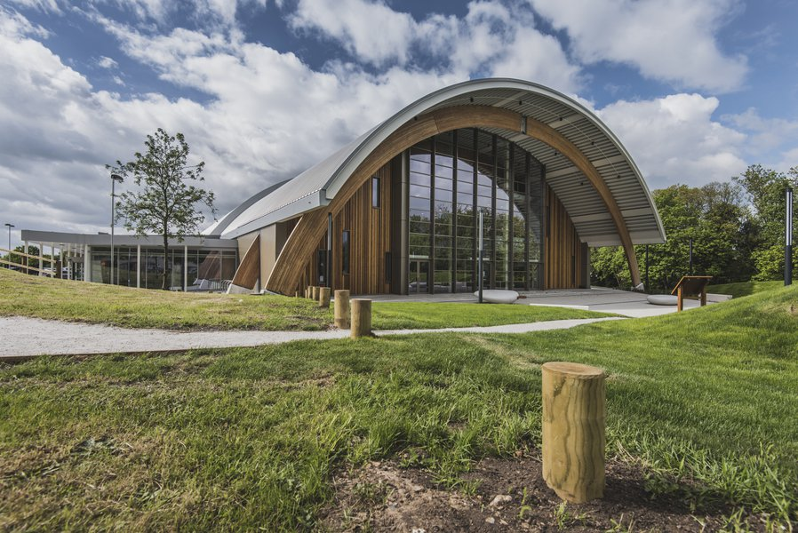 A view from the outside of the Montem Ice Arena in Slough, the building has a curved roof and surrounded by green public space