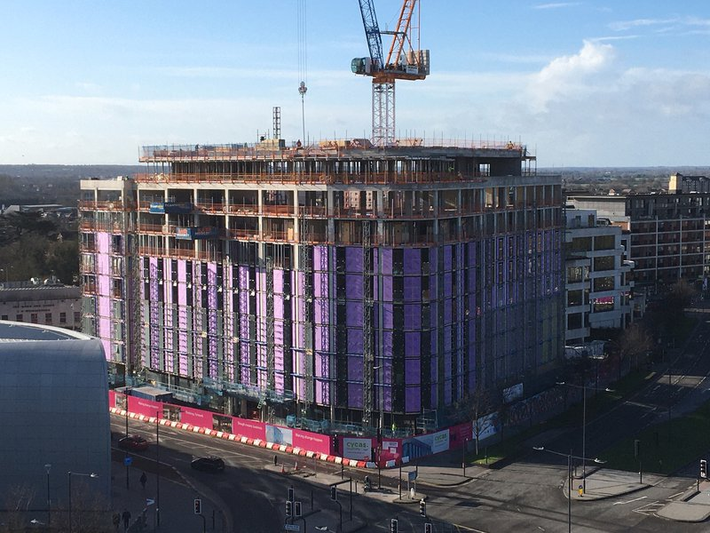 The Moxy Hotel in the construction phase, shows the complete square building from a distance with scaffold and purple building wrap