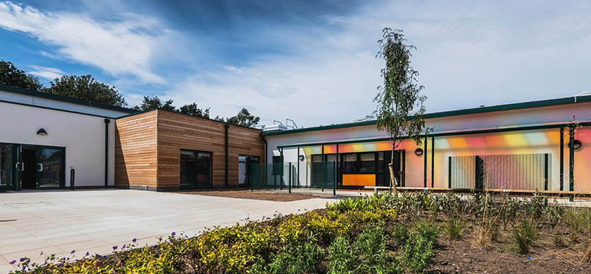 Image of the outside of the The Bridge SEN School, with brightly coloured sun shade to the front of the building