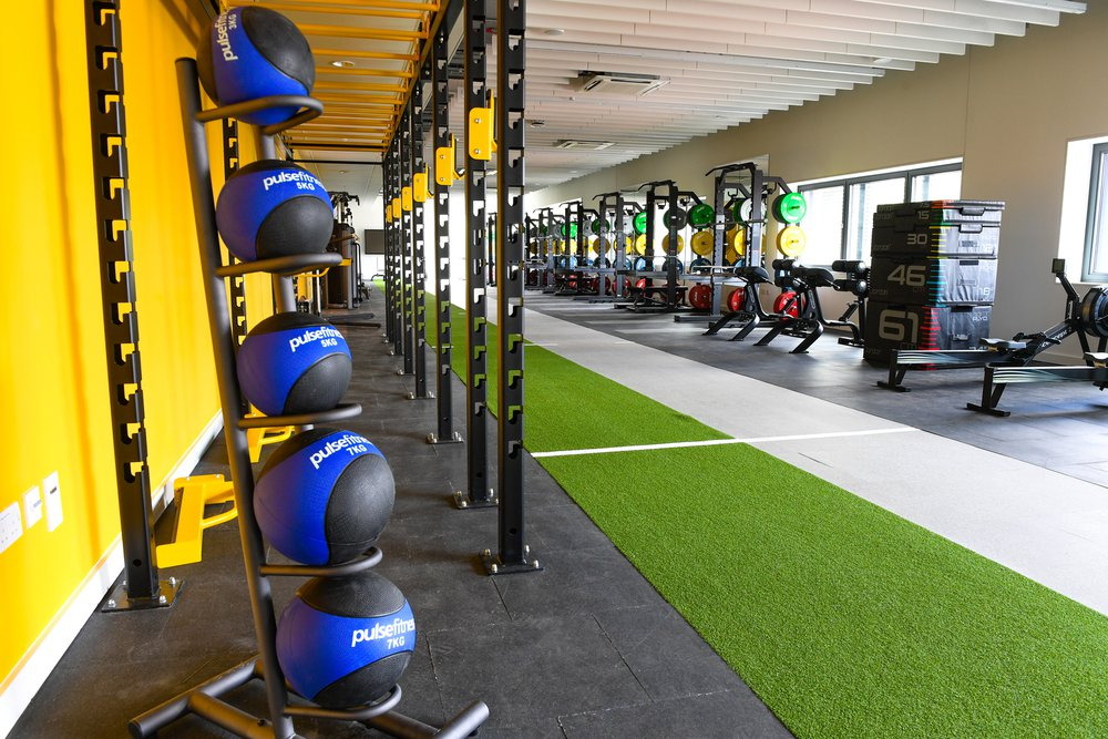 Gym area at Southampton Solent Sports Complex, image focuses on dumbells which are next to a bright yellow wall