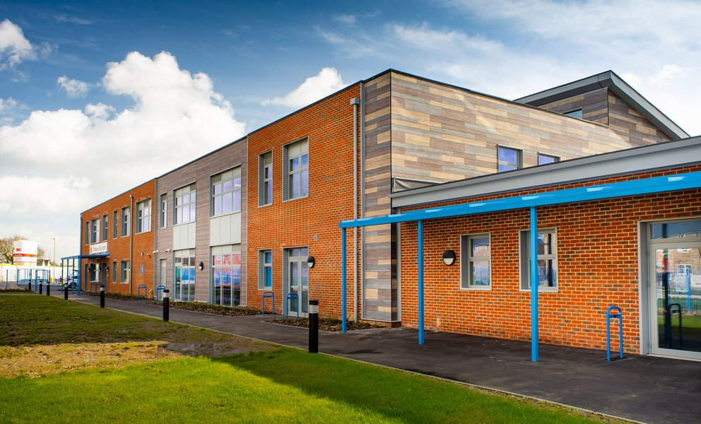 Front view of Hailsham School showing the orange brickwork and grey, blue and cream cladding to the right hand side
