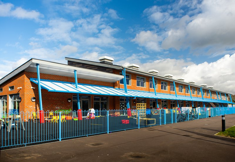 View of the enclosed playground at Hailsham School, with bright blue railings around the outside