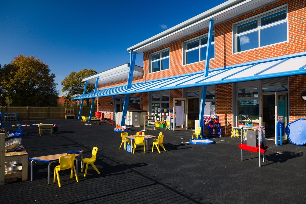 View of the playground area in front of the Hailsham School building, which features wooden tables and yellow seating