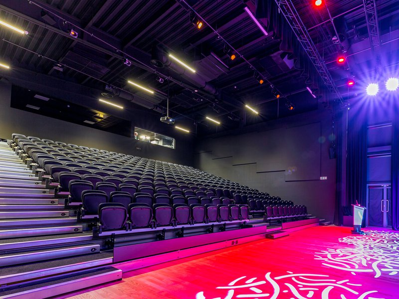 The 300 seat theatre building at Torquay Academy, with the pink, orange and purple lighting the stage area