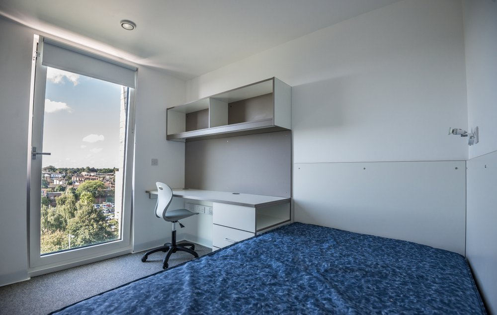 Image of a completed student accommodation bedroom with large window, desk and bed