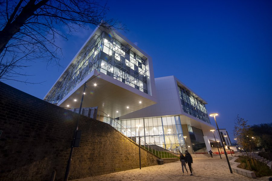 A couple walking past the Barbara Hepworth Building at the University of Hudderfield in the evening