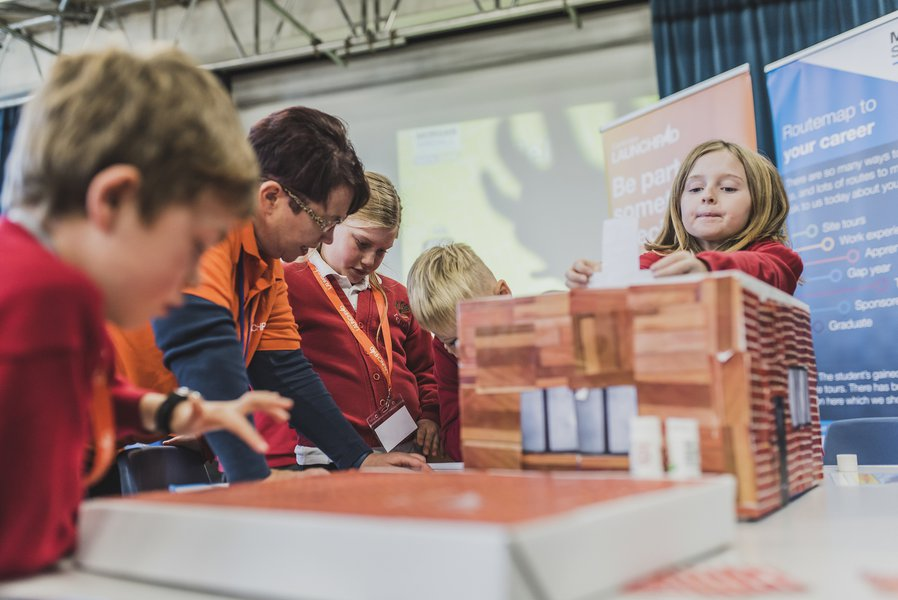 Helen Clements and a group of pupils taking part in a Build your Own School project at a school careers event