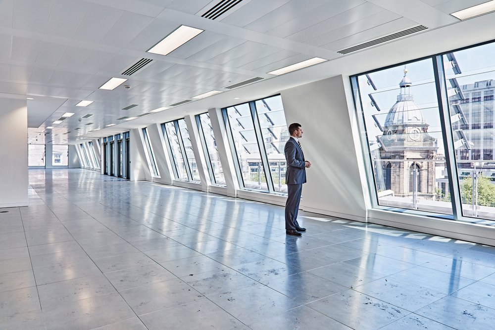 Man stands in the window of the Colmore Row office overlooking Birmingham Cathedral