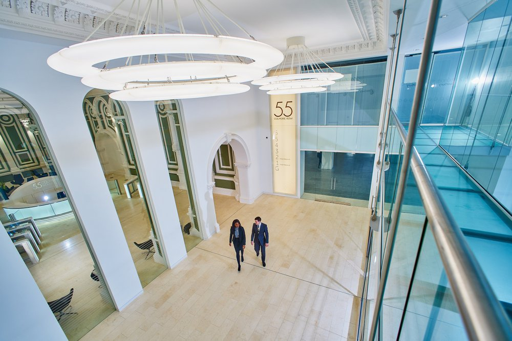 Two people standing in the reception area of 55 Colmore Row, next to a seven story glass lift system