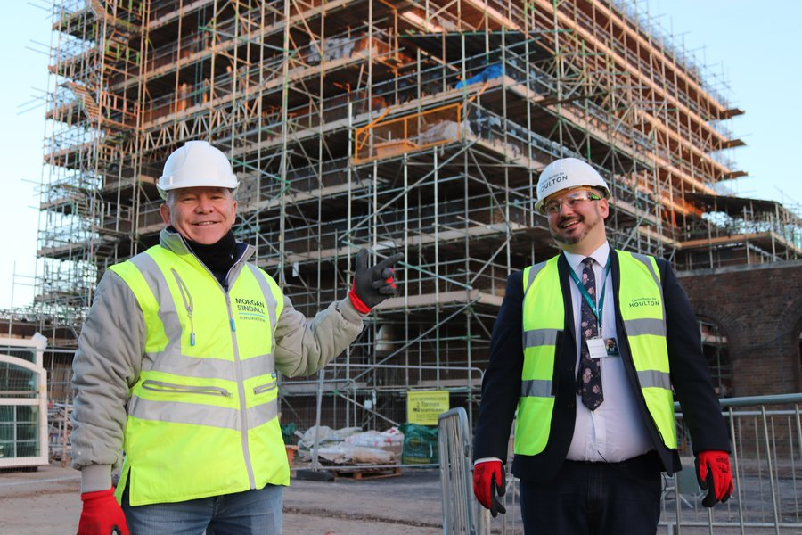 Picture of BBC presenter Dominic Littlewood and the Headteacher of Houlton School outside the front of the Houlton School construction site