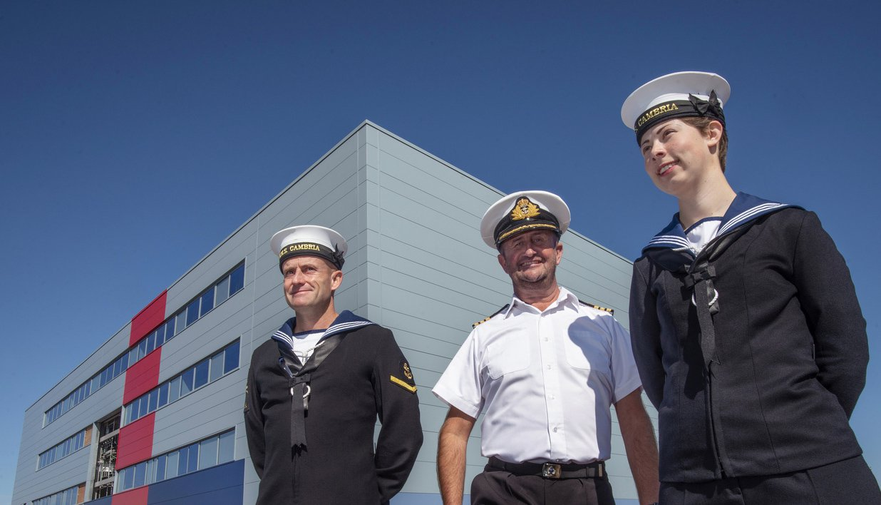 Two male and one female Royal Naval personnel outside of the HMS Cambria building