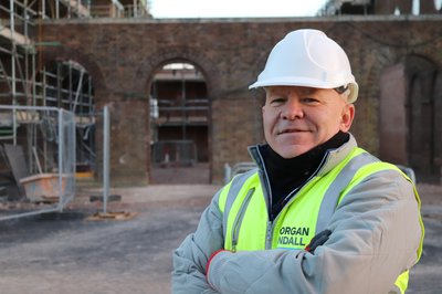 Picture of BBC presenter Dominic Littlewood in high-vis outside the Rugby Radio/Houlton School project