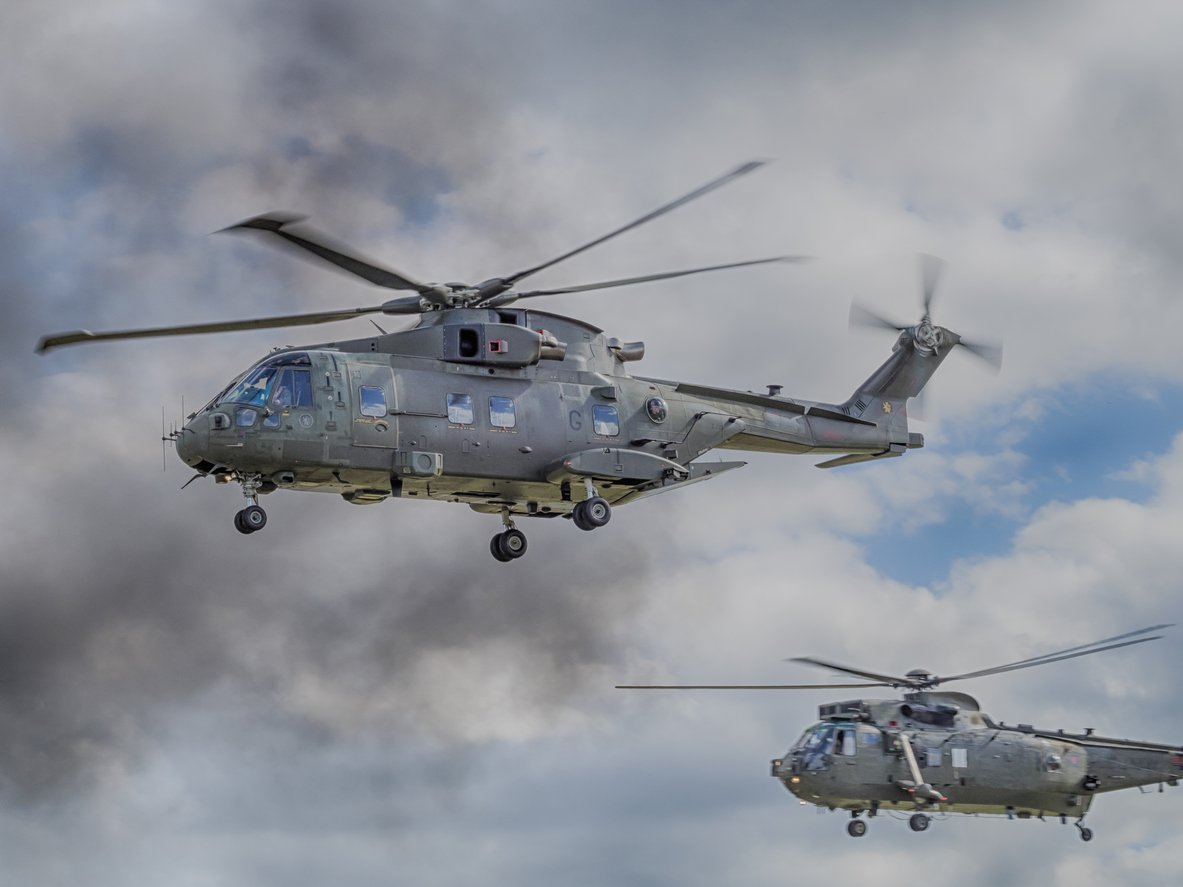 Two army helicopters flying in the sky