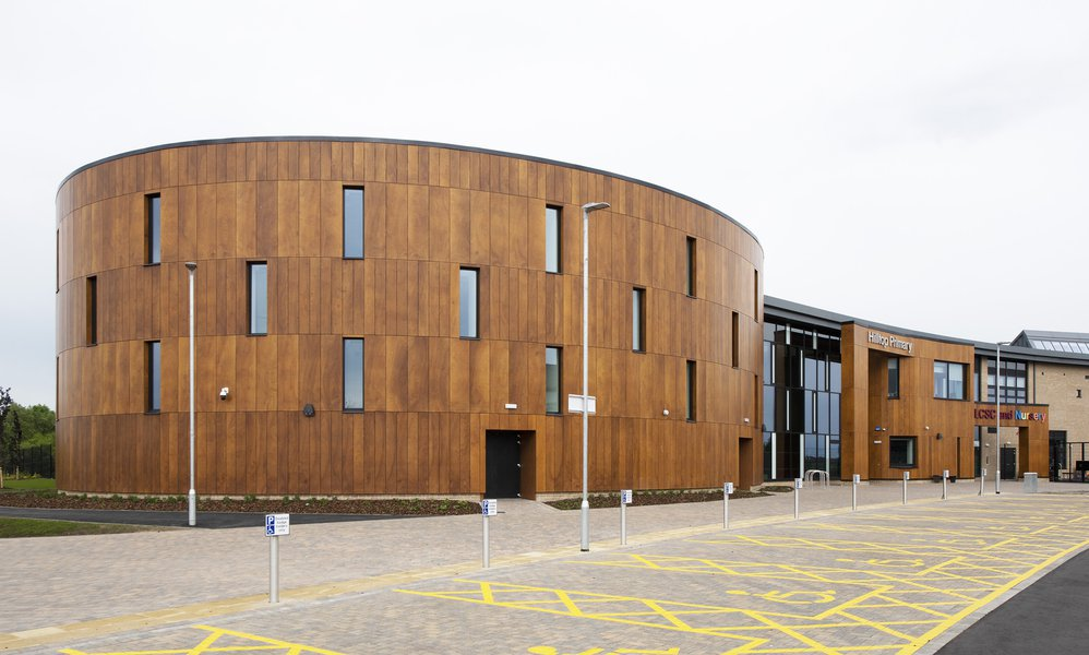 View of the curved sports hall at Hilltop Primary School from the outside, showing the wooden cladding