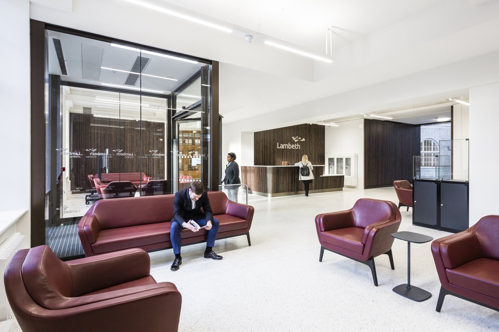 A reception area of the Lambeth Town Hall Building with purple sofas and large reception desk