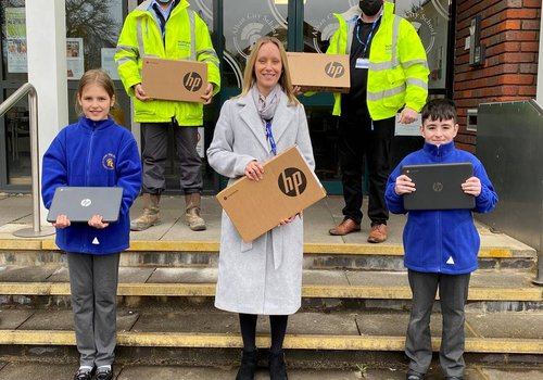 The CCOS team pictured outside Alban City School with laptops they'd donated