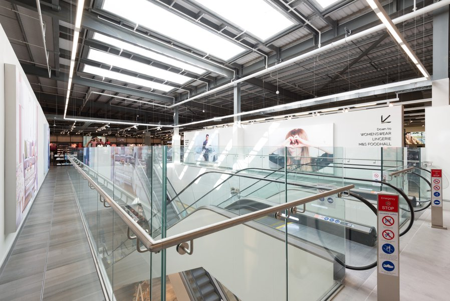 A picture of the escalator system in the middle of a department store, part of Longbridge Shopping development