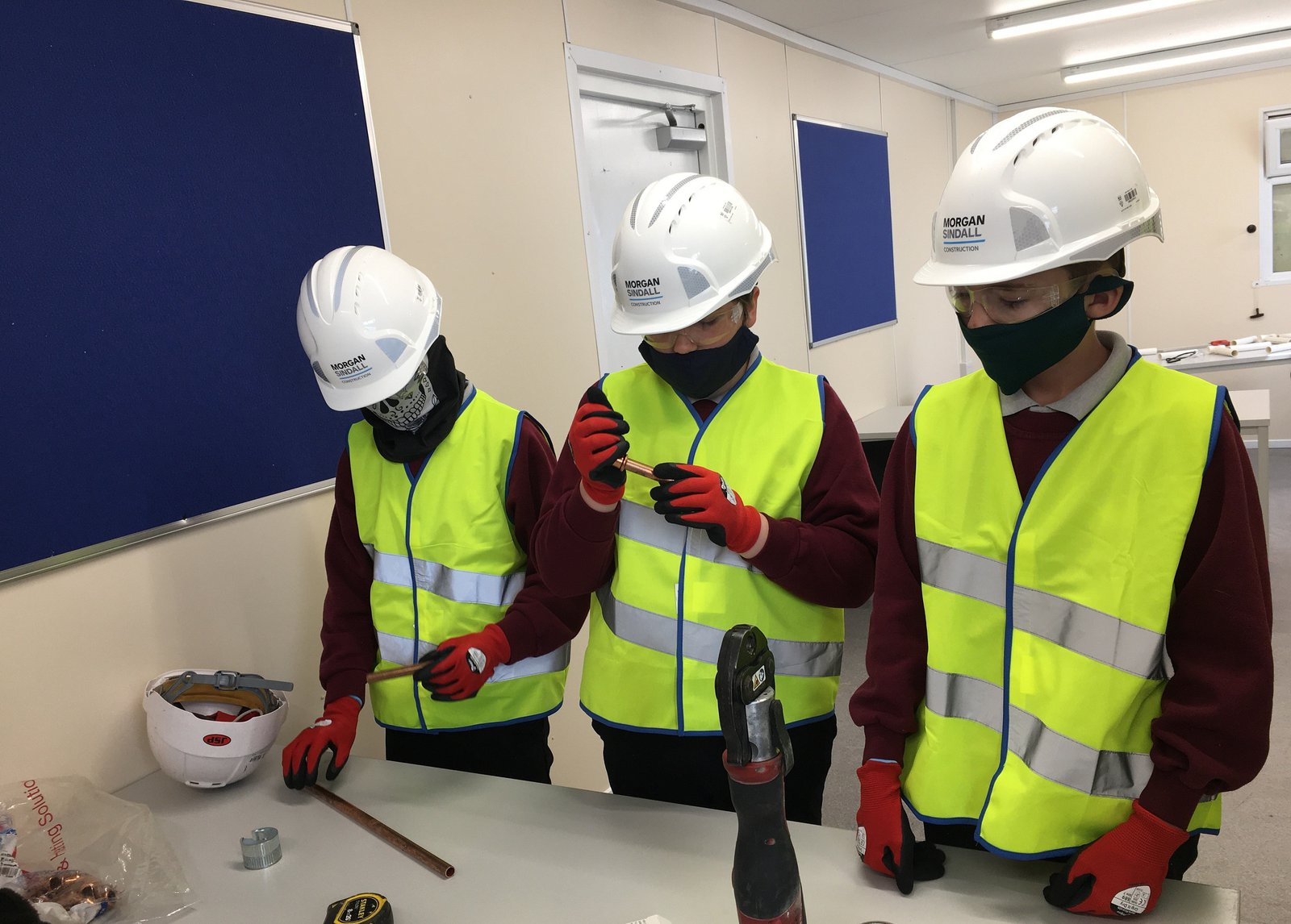 Three students taking part in a construction workshop