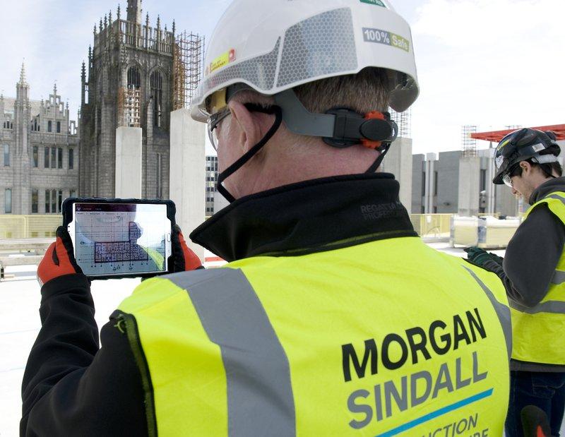 A man looking at a BIM model on an ipad