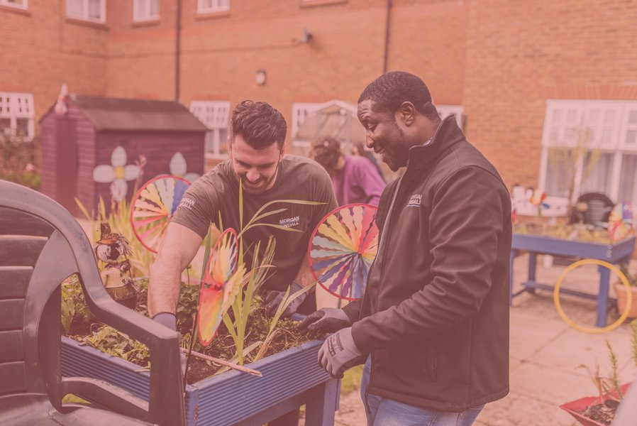 Two Morgan Sindall Construction employees planting a planter box at a charity event - Give and Gain Day