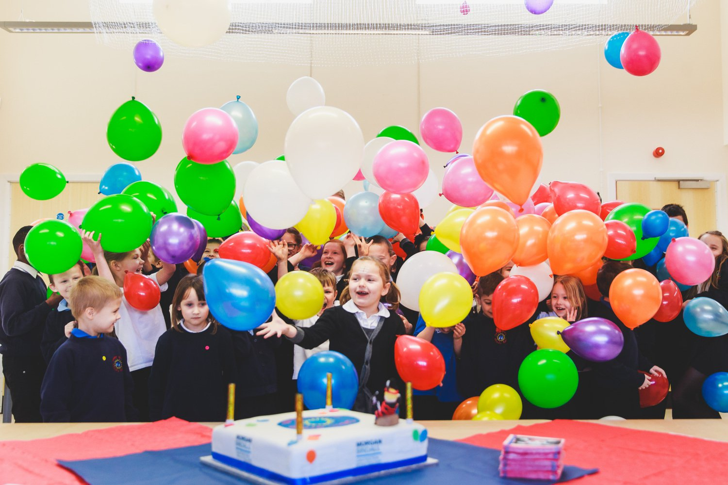 A group of happy school pupils playing with balloons, as part of a balloon drop that was organised for a school handover