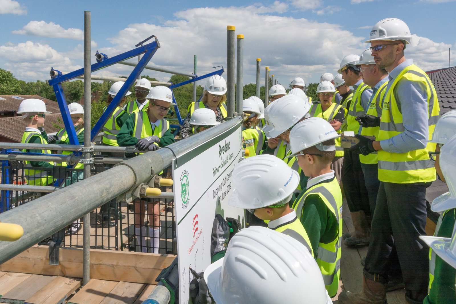 Pupils draw their self portraits on a board provided at the Ryedene School topping out ceremony