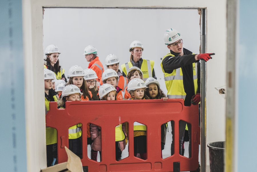 A site tour taking place on a Morgan Sindall Construction site with a group of primary school children and their teachers