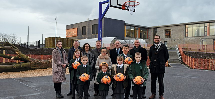 The Morgan Sindall Construction team and teachers and Pupils from St Nicholas' Primary standing on the new basketball court