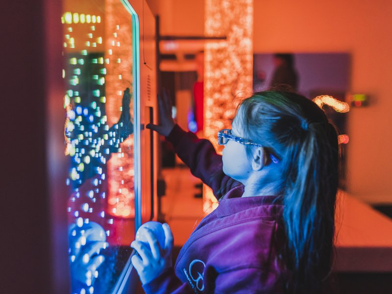 Image of a child in the sensory room at Glenwood SEN School in Essex, she is using one of the sensory bubble machines