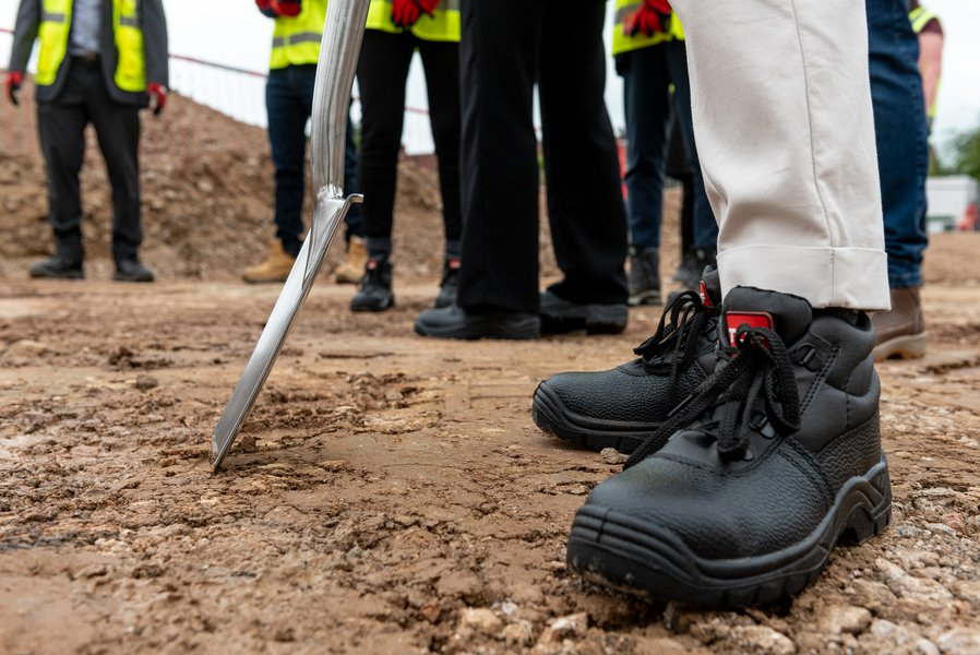 Picture of someone placing a spade into the ground at the Groundbreaking event at Ravensdale School