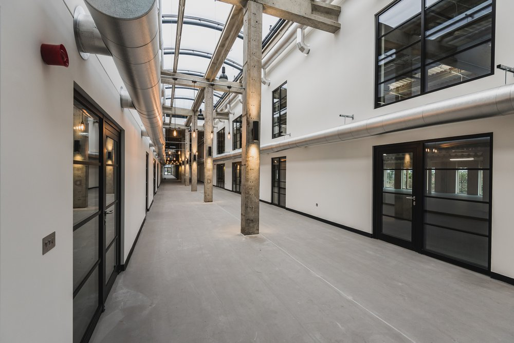 View of the corridor of the Sawston Unity Campus building, which is made light and airy due to the glass panel roof