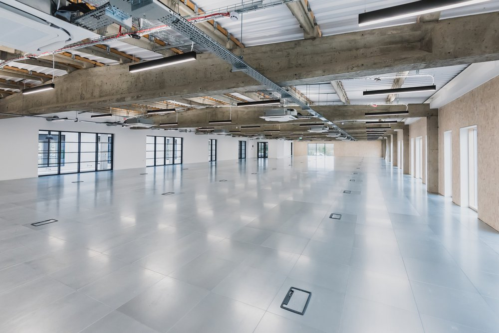 Contemporary office space at the Unity Campus project which includes polished concrete floor and exposed pipework ceiling