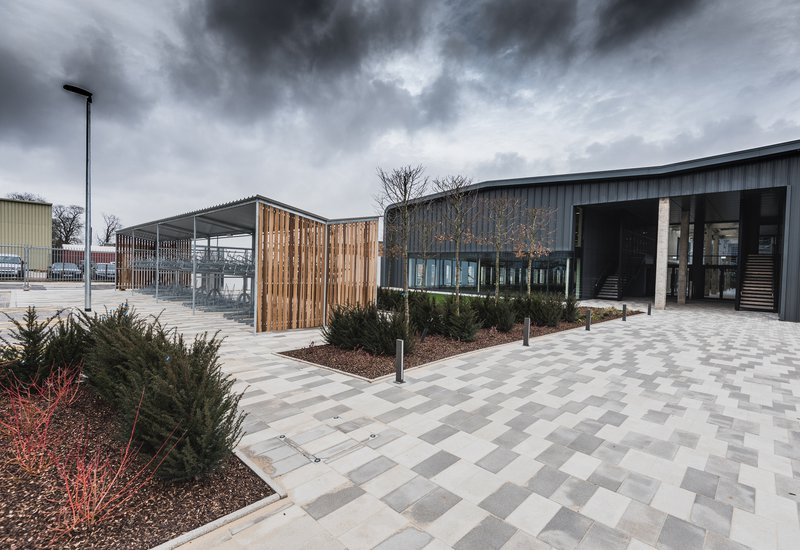 Image of the front entrance of the Unity Campus building in Sawston, Cambridge that shows the block paving and planting to the front