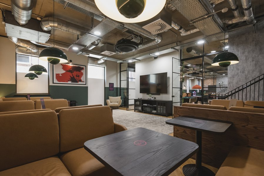 Common room area with TV, sofa and tables at the Vita Student accommodation in Nottingham