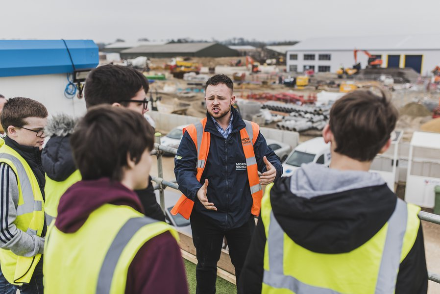 Image of Morgan Sindall Construction project manager, showing a group of students around the West Suffolk Operational Hub construction site