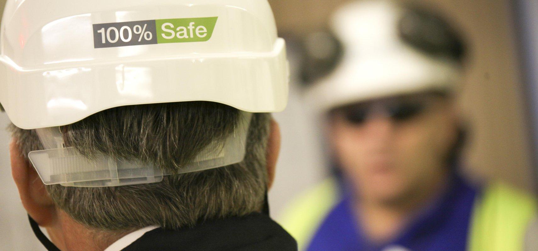 Individual wearing hard hat showing 100% safe