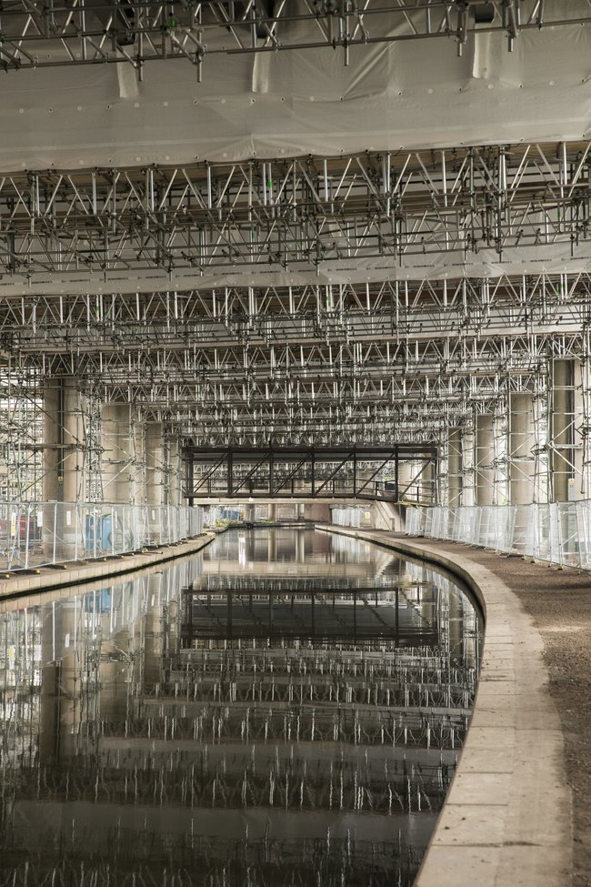 A view from beneath the M5 Oldbury viaduct project, showing the scaffolding and its reflection in a canal passing beneath the bridge.