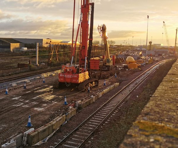Various site equipment is shown beside a railway track. The sun is setting in the distance.