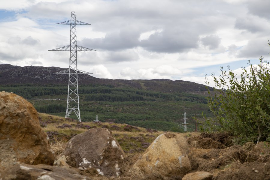 A pylon and overhead lines are depicted against the countryside on our SSEN Knocknagael to Tomatin project..