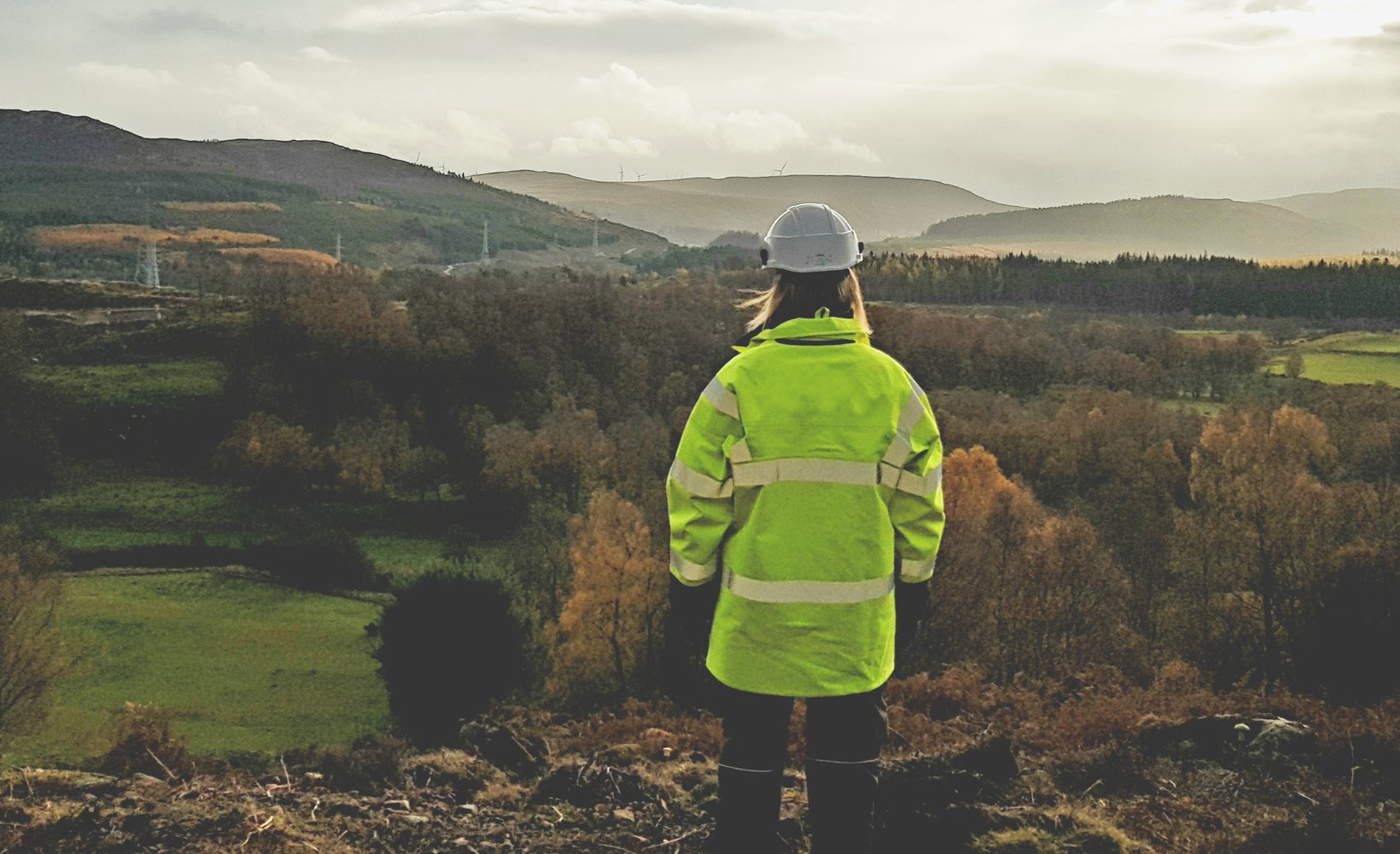 A person wearing Personal Protective Equipment stands with their back to the camera, facing an expanse of countryside that stretches to the horizon