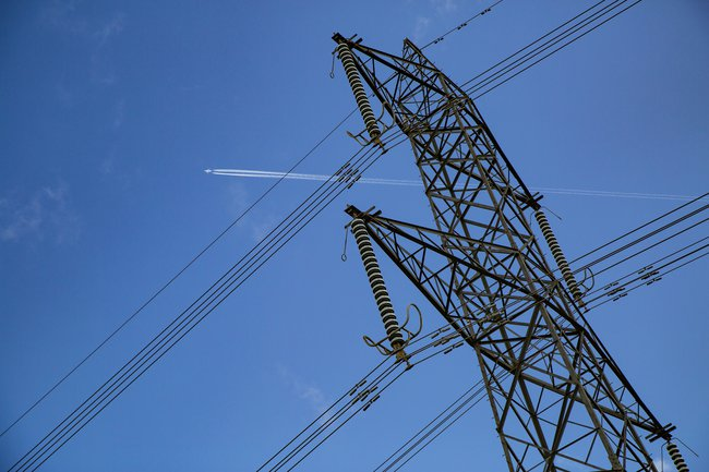 A pylon and overhead lines are depicted against a blue sky on a sunny day.