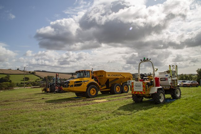 Three items of site machinery, a truck, tractor, and small wagon, are parked in a field.