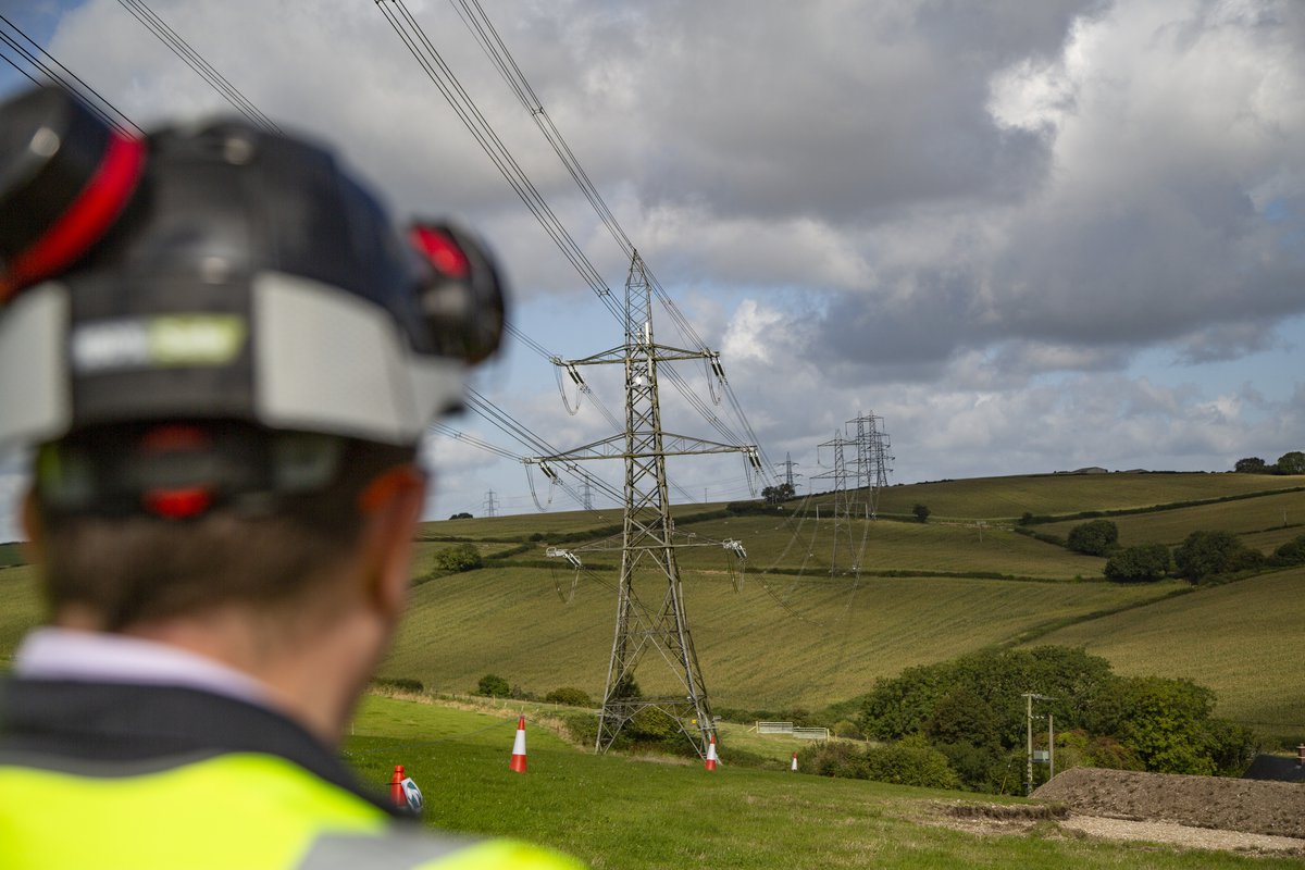 A man wearing Personal Protective Equipment is facing away from the camera, looking towards the project. Pylons and overhead line cables are visible in the distance.