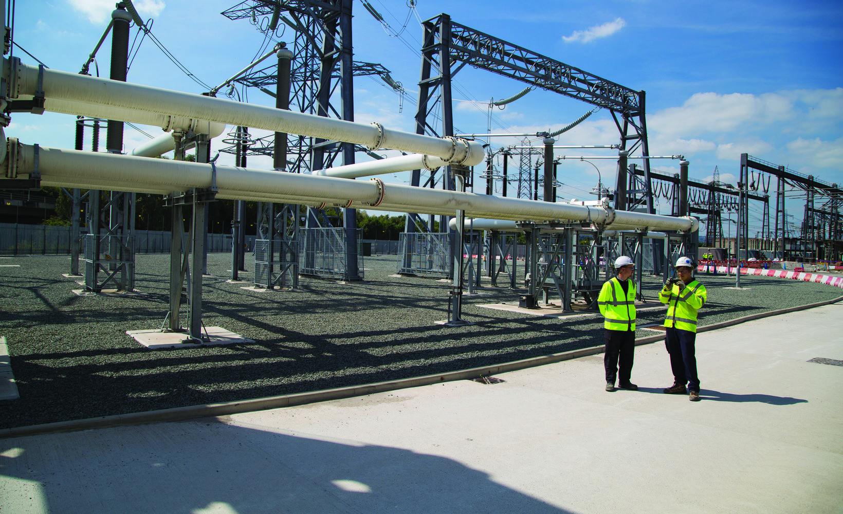Two colleagues stand in front of a large assembly of pipes, electricity apparatus and an electrical tower, which connects to power lines that stretch off into the distance