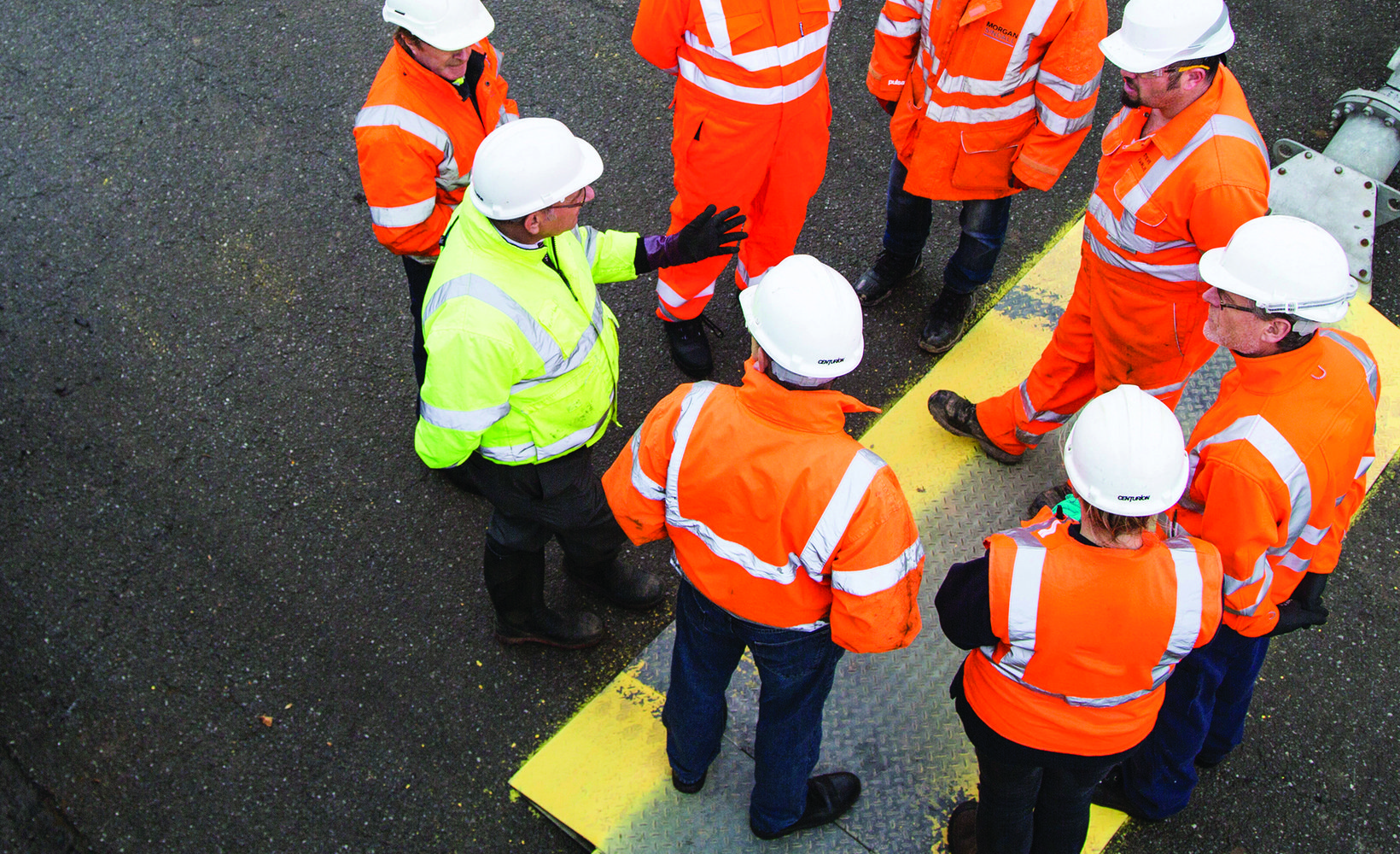 Eight colleagues stand in a circle, wearing Personal Protective Equipment, having a conversation