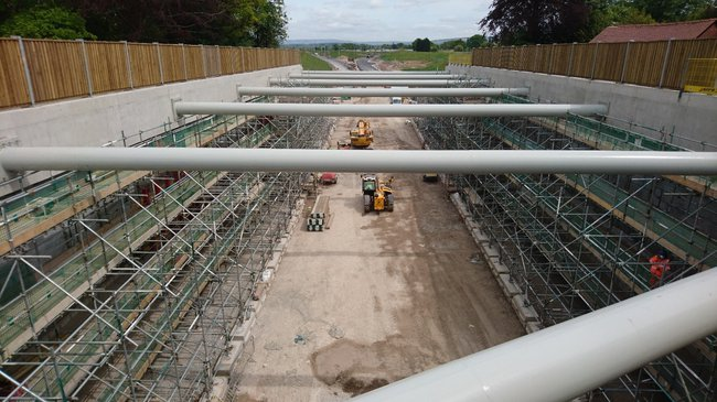 A view through metal bars showing a road under construction with scaffolding lining both sides of a cutting into the ground.