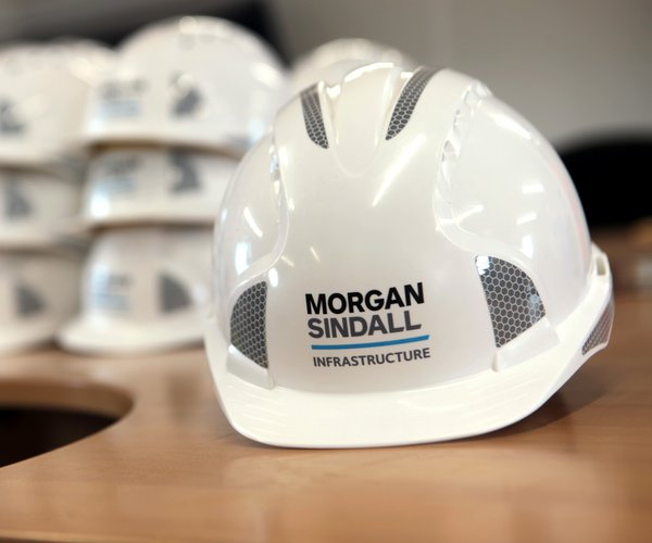 A Morgan Sindall Infrastructure hard hat is depicted on a table. In the background, several other hard hats are stacked on top of one another.
