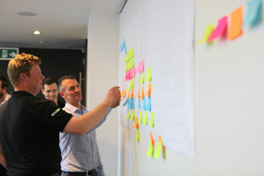 A group of male colleagues takes part in an exercise in an office, adding paper notes to a wall