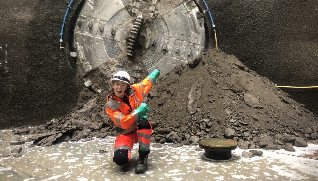 A female colleague wearing Personal Protective Equipment kneels in front of a Tunnel Boring Machine, smiling and pointing towards it